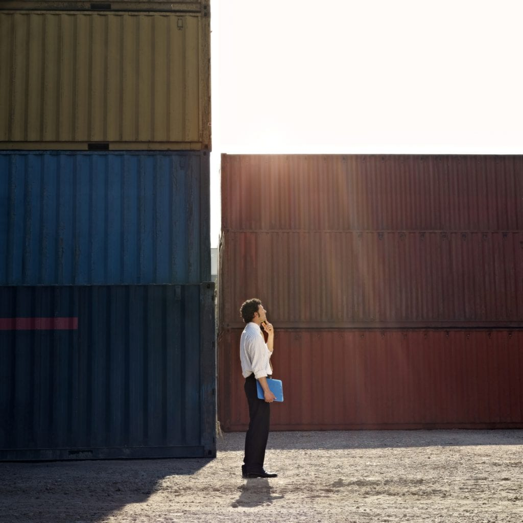 Man stands in front of shipping containers to illustrate how to build a shipping container home
