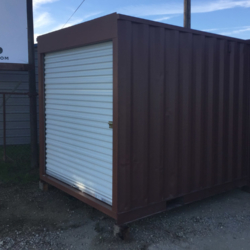 Shipping container with roll up door