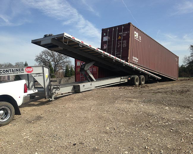 Tilt bed trailer placing a shipping container