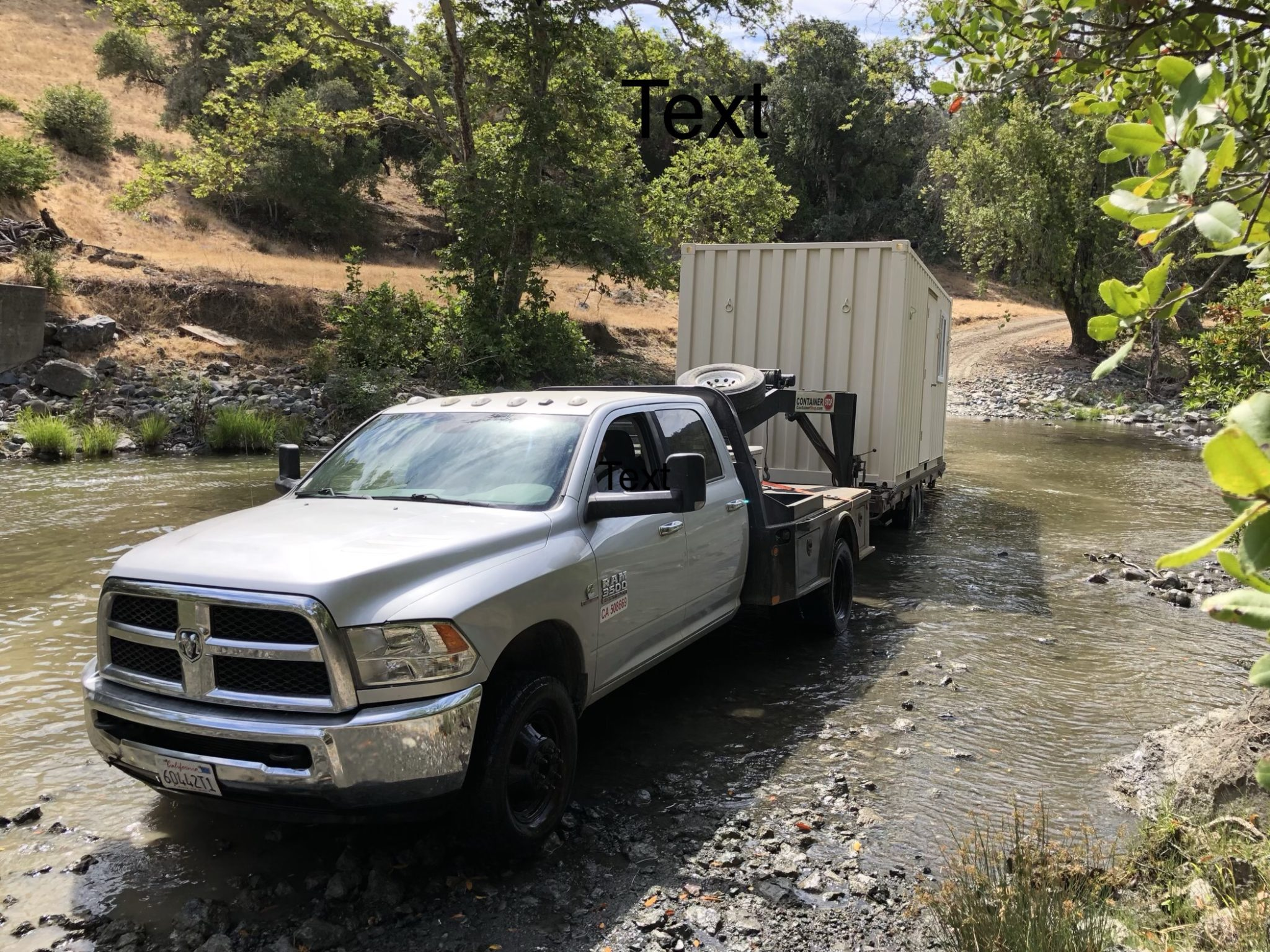 Truck delivering a storage container over a stream
