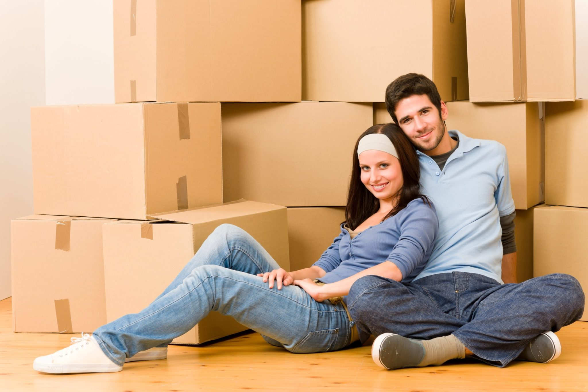 Happy couple in front of a wall of packed moving boxes to illustrate What's Living In A Shipping Container Like